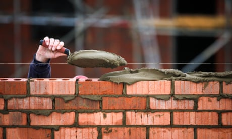 A construction worker holds a trowel of                       cement as he lays bricks at a construction site