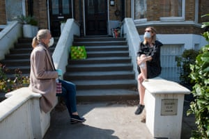 Neighbours near Primrose Hill, chatting on front steps, wearing face masks, during the coronavirus pandemic lockdown