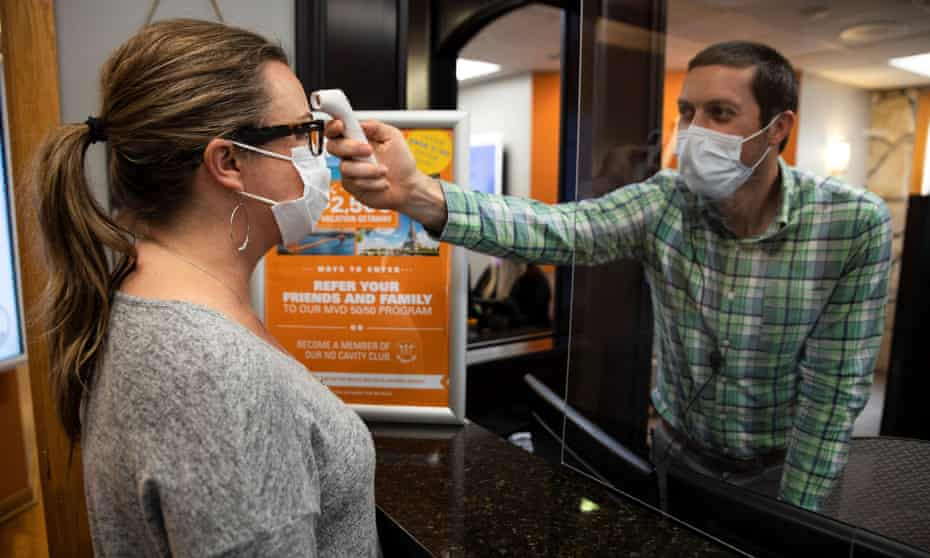 A dentist office manager takes the temperature of a woman as Ohio implements phase one of reopening dentists, veterinarians and elective surgeries on 1 May.