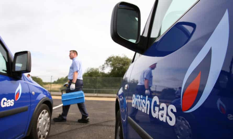 Photograph looking down the sides of two British Gas vans parked next to each other towards an engineer walking past them with a toolbox in hand