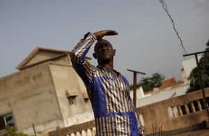 Designer Baba Sereme poses in a bazin outfit he dyed at his home in Bamako