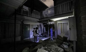Residents walk past debris at the damaged American Quality Lodge where they continue to live in the aftermath of Hurricane Michael, in Panama City, Florida, on 16 October.