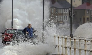 A man gets caught in spray as a high tide breaches the sea wall throwing up debris and flooding the main road in the village of Carnlough, Northern Ireland, on December 20.