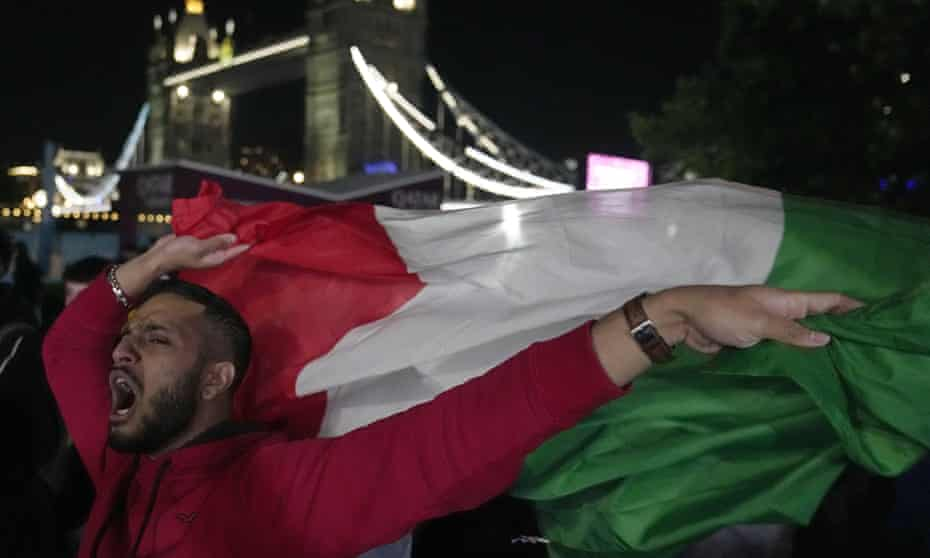 An Italian supporter celebrates Italy's victory over Spain at the fan zone in Potters Field in London.