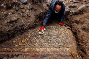 An archaeologist inspects a 1,500-year-old mosaic discovered in a Roman-era monastery in Ìzmir, Turkey