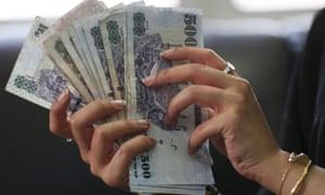 A Saudi woman counting riyal banknotes.