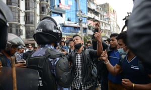 Nepalese police push back residents who began protesting after waiting for hours in line to board buses back to other towns and villages from Kathmandu.