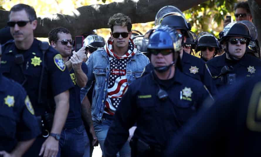 Milo Yiannopoulos is escorted by police officers after speaking during a free speech rally on 24 September 2017 in Berkeley, California.