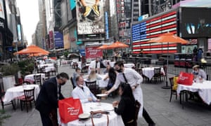 Servers deliver food to a table at a pop-up restaurant set up in Times Square, New York, in October.