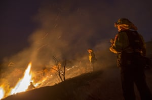 Firefighters watch a colleague emerge from fighting flames in chaparral brush using only a hand tool at the La Tuna Fire near Burbank, California.