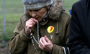 A supporter of the SOS Defense of Unborn Life Foundation kisses a rosary while demonstrating against abortion in Warsaw last month.