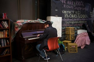 A passerby stops and plays a piano, much to the delight of the crowd