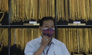 A Thai shopkeeper adjusts his face mask at a gold shop in Bangkok, Thailand. The price of gold surged more than $30 on Monday, July 27.