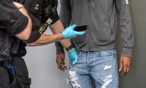 A suspect has his pockets searched by police officers