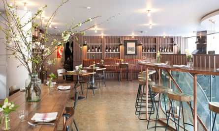 Slim pale wood tables and chairs, with a bar and wine bottles and bright lighting in the The Other Naughty Piglet