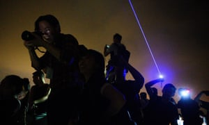 Pro-democracy activists react as they take photos while another person uses a laser pointer on Lion Rock.