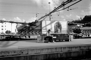 Zurich railway station: a woman sits on a metal bench reading. In the background two military tanks are being transported by train