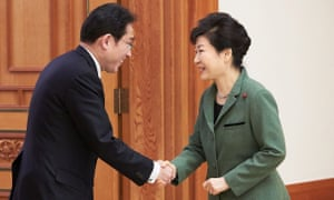 South Korea's president Park Geun-hye (right) shakes hands with Japan's foreign minister Fumio Kishida on 28 December.