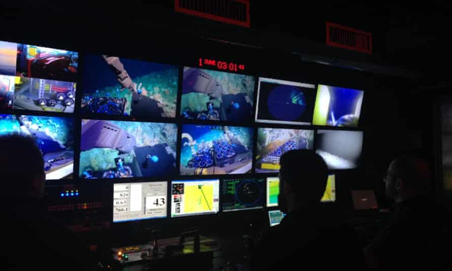 Scientists look at screens in a control room as they operate deep-sea submersibles remotely