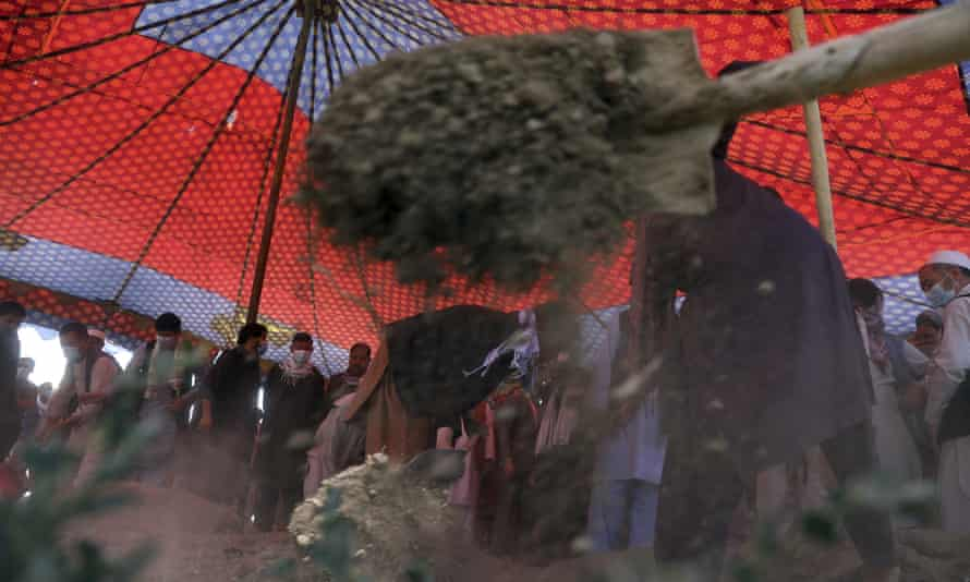 A shovel of dirt is thrown on a grave in Kabul, as Hazara men stand in the background