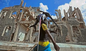 A fisherman carries a sailfish past buildings destroyed in the warfare.