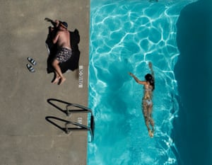 In the apartment's open-air pool, the girl swims while the man sunbathes