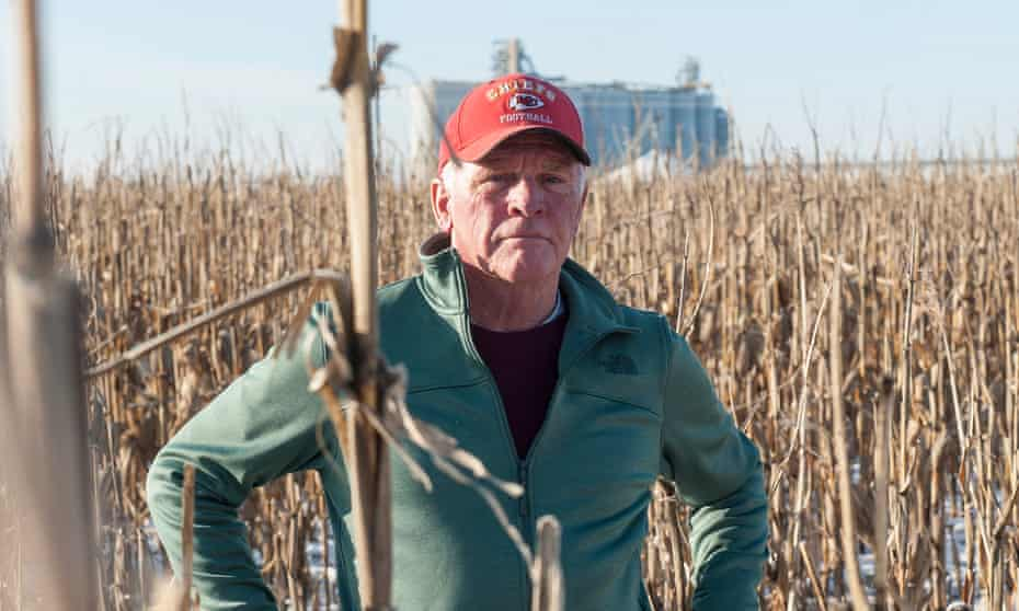 Richard Oswald stands in a frozen puddle surrounded by unharvested corn. Wet conditions have made harvesting difficult for Oswald and other farmers.