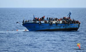 People jump out of a boat right before it overturns off the Libyan coast