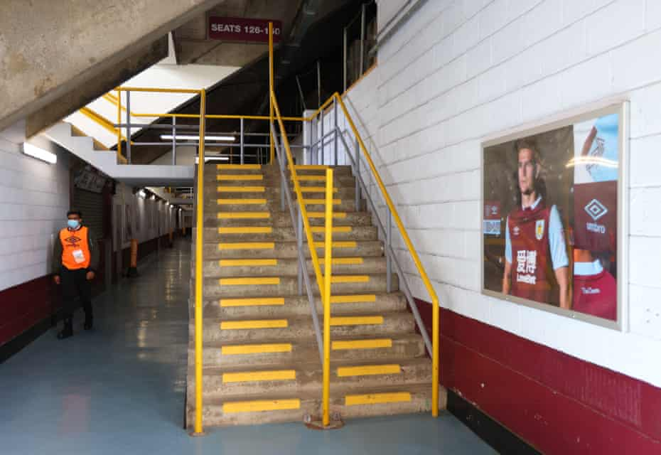 A steward walks through the empty stands at Turf Moor prior to the Premier League match between Burnley and Brighton & Hove Albion in July.