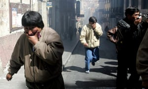 Bolivian mine workers run and take cover from tear gas during a demonstration in La Paz, Bolivia, May 18, 2005