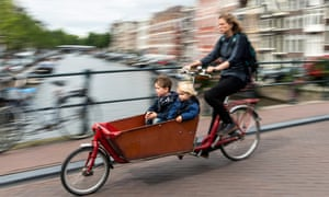 A woman and children cycling in Amsterdam.