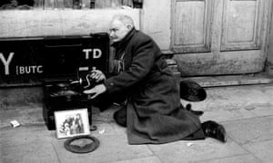Mr William East cranks his gramophone handle as he begs on the streets of London in May 1969.