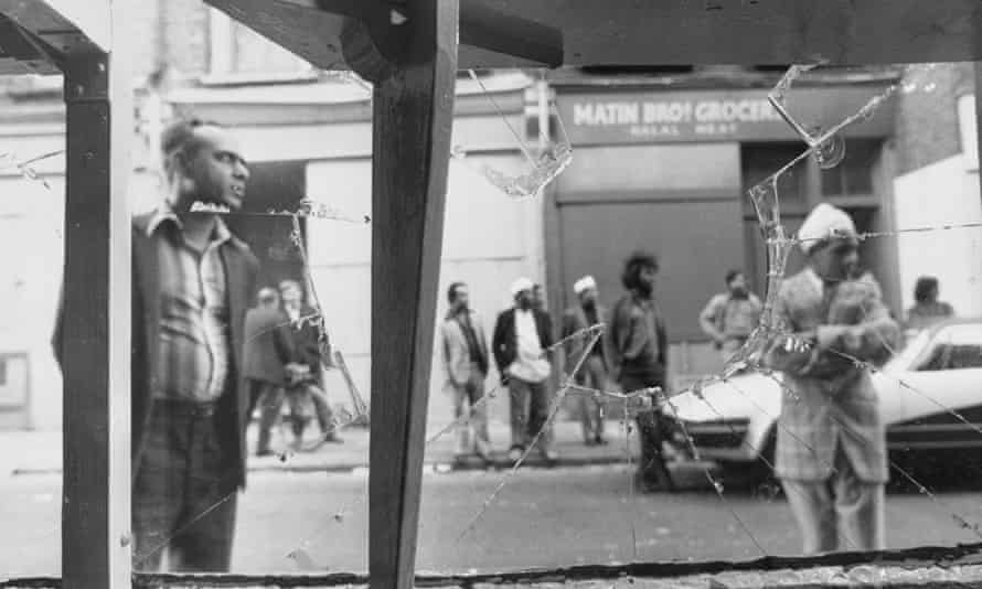 A businessman examines the broken window of his shop, damaged in a race-related incident in Brick Lane in 1978.