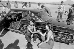 Two friends pose for their photograph in front of a prize-winning car at a low riders meeting on the outskirts of Phoenix, 1979.