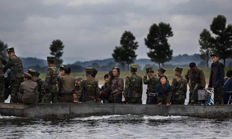 North Koreans ride on a boat used as a local ferry as they cross the Yalu river north of the border city of Dandong, Liaoning province, northern China near Sinuiju, North Korea.