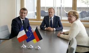 French President Emmanuel Macron, left, European Council President Donald Tusk, center, and German Chancellor Angela Merkel
