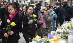 People place flowers at a memorial for the victims of Monday's van attack in Toronto