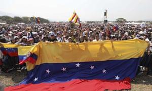 Concert goers unfurl a large Venezuelan flag during the Venezuela Aid Live concert