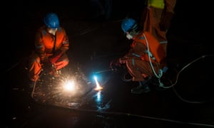 Rescue workers cut into the upside-down hull of the Eastern Star on Wednesday as they work around the clock at the capsize site in the Yangtze river.