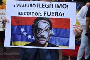 """A sign reading """"Maduro, illegitimate, dictator get out!"""" is held in a protest by Venezuelans outside their embassy in Guatemala City in support of opposition leader Juan Guaido's self-proclamation as acting president"""