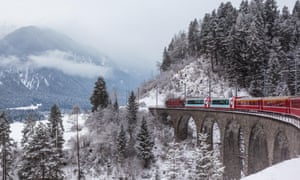 Famous tourist train running over overpass in Switzerland, Glacier Express in winterG0TX2B Famous tourist train running over overpass in Switzerland, Glacier Express in winter
