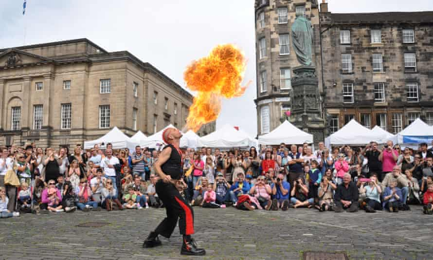 A street performer fire-eating in front of a large  crowd at the festival in pre-pandemic times.