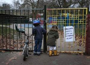 Children look into a closed playground next to Battersea Park in London, England.