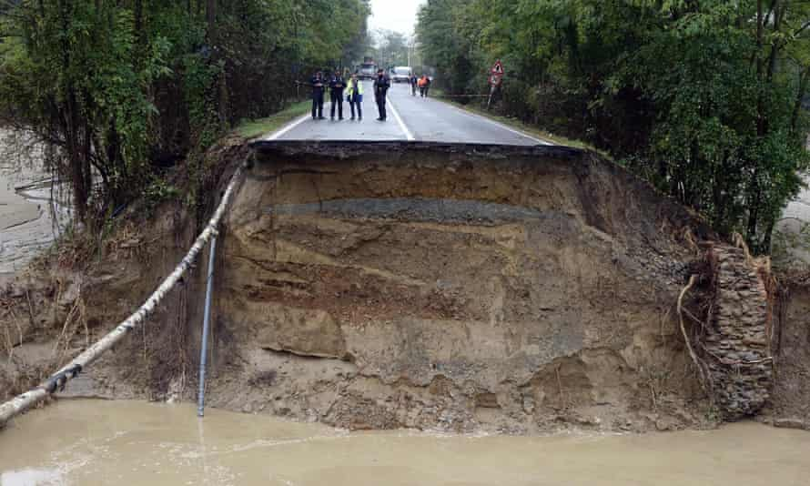 A collapsed road in Piedmont, Italy. Two people are dead and two others are missing after a wave of storms in northern Italy.