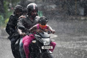 Chennai, India. A family rides on a motorbike during a heavy rain shower