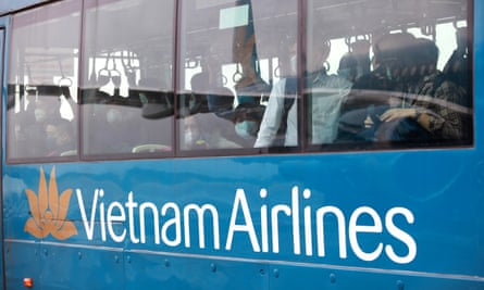 Passengers wearing masks stand in a bus after disembarking a Vietnam Airlines plan