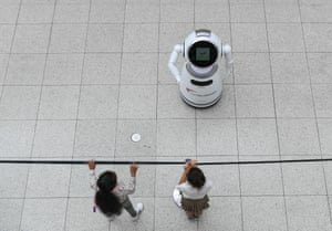 Children watch a smart robot explaining Covid-19 prevention measures at a shopping mall in Frankfurt, Germany