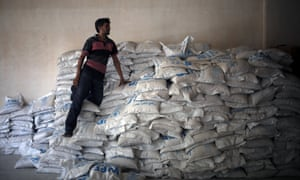 A Syrian man stands on aid parcels from the UN World Food Programm (WFP) and the Syrian Arab Red Crescent in Saqba, Syria.
