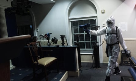 A member of the cleaning staff dressed in a protective suit, sprays the James Brady Briefing Room of the White House.