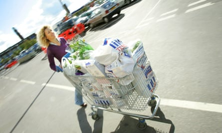 A woman pushes a Tesco trolley full of shopping